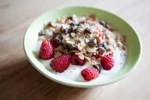 Fresh raspberries an oat flakes in bowl of yogurt on wooden surface